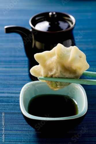 Pasta parcel on chopsticks above soy sauce