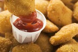 Dipping a chicken nugget in ketchup