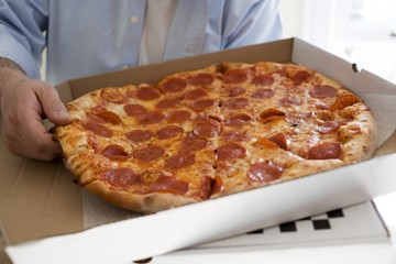 Man holding pizza box containing pepperoni pizza