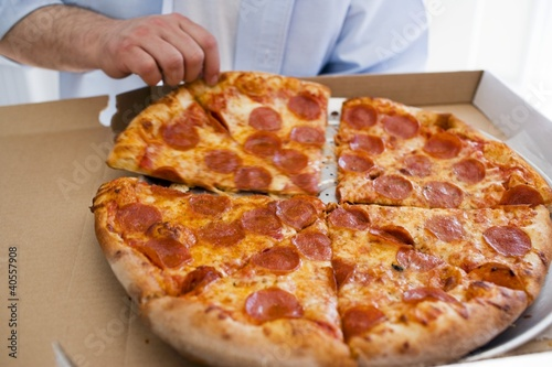 Hand taking piece of pepperoni pizza out of pizza box