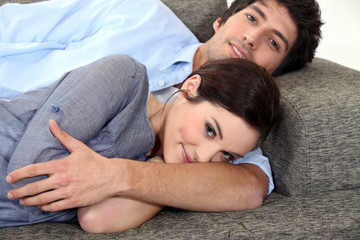 Couple lying on sofa