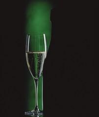 Glass of sparkling wine beside wine bottle in green light