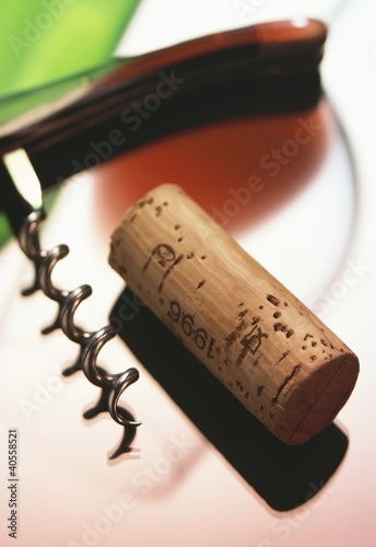 Wine cork, corkscrew and glass of red wine