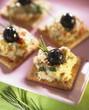 Aubergine cream and black olives on crackers