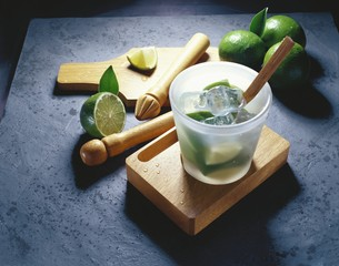 Limes and ice cubes in a glass with a pestle