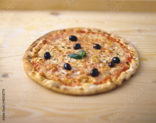 Pizza with black olives, basil and oregano