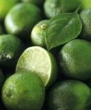 Limes, several whole and one halved (full-frame)