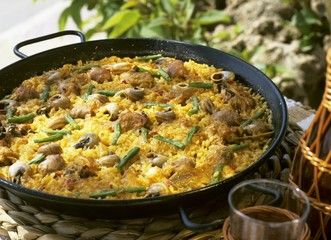 Paella (rice dish) with meat, vegetables and snails