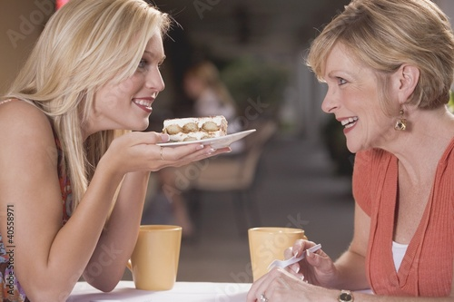Two women in a café with a piece of tiramisu
