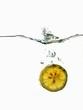 Slice of lemon falling into water