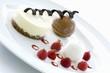 Small cakes, ice cream and raspberries on dessert plate