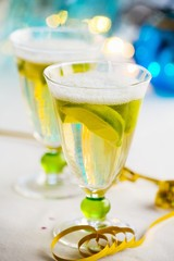 Two glasses of sparkling wine with lemon wedges