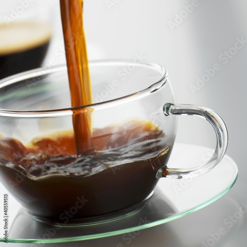 Pouring coffee into a glass cup