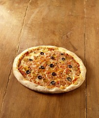 A pizza with mushrooms & black olives on wooden background