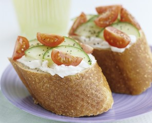Soft cheese, cucumber and tomato on baguette slices