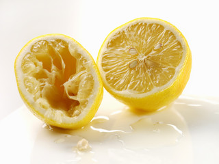 Two lemon halves, one squeezed