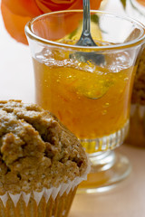 Orange marmalade in a glass, a muffin in front