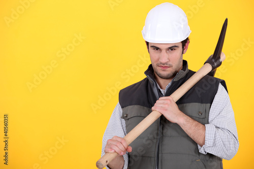 craftsman holding pickaxe against yellow background