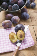 Fresh damsons, one halved with knife
