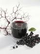 A glass of elderberry & apple juice & fresh elderberries