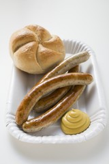 Four sausages with mustard and bread roll