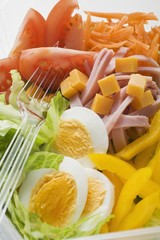 Mixed salad with ham and egg in plastic container