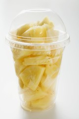 Pineapple chunks in a plastic cup with a lid