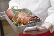 Rolled saddle of suckling pig in roasting tin with rosemary