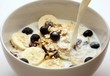 Pouring milk onto muesli with bananas and blueberries