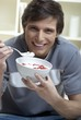 Young man eating quark with fresh strawberries