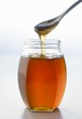 Honey running from spoon into jar