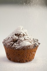 Sprinkling a chocolate muffin with icing sugar