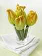 Five courgettes with flowers in a glass on a napkin