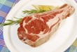 Raw lamb chop on a plate, rosemary, lemon