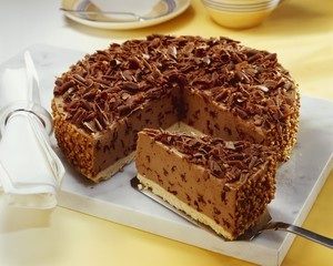 Hazelnut chocolate cheesecake with grated chocolate, a piece cut
