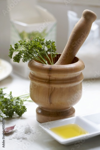Wooden pestle & mortar with ingredients for parsley pesto