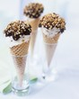 Three cones of stracciatella ice cream with chocolate & nuts