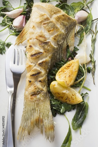 Fried sea bass with herbs, garlic and lemon