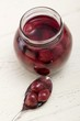 Cherry compote in jar and on spoon
