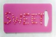 The word 'Sweet' written in sweets on pink chopping board