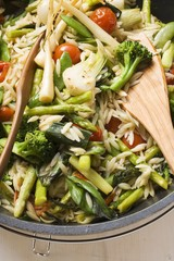 Orzo (rice-shaped pasta) with vegetables (overhead view)