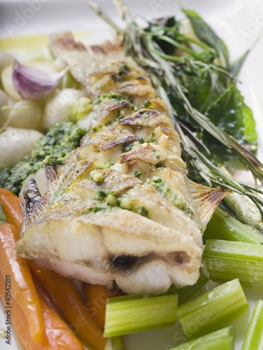 Fried sea bass with pesto on vegetables