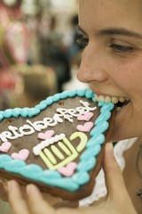 Woman biting into Lebkuchen heart at Oktoberfest