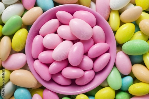 Sugared almonds, in and around pink bowl