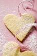 Pastry hearts with icing sugar and pink ribbon