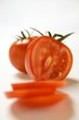 Two tomatoes, one partly sliced