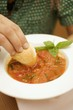 Hand dipping white bread into tomato soup with basil