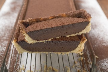 Rectangular chocolate tart with cocoa powder, partly sliced
