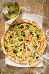 American-style vegetable pizza, a slice cut, olive oil