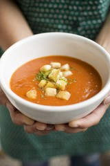 Hands holding bowl of tomato soup with croutons